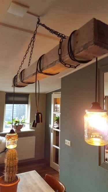 Lamp pallethout en lege potjes.  Pallet planken aan elkaar geschroefd, toen een ketting eraan vast gemaakt. Daarna de bedrading, en touw om lege groente potjes gedaan. Resultaat is een unieke zelfgemaakte lamp.