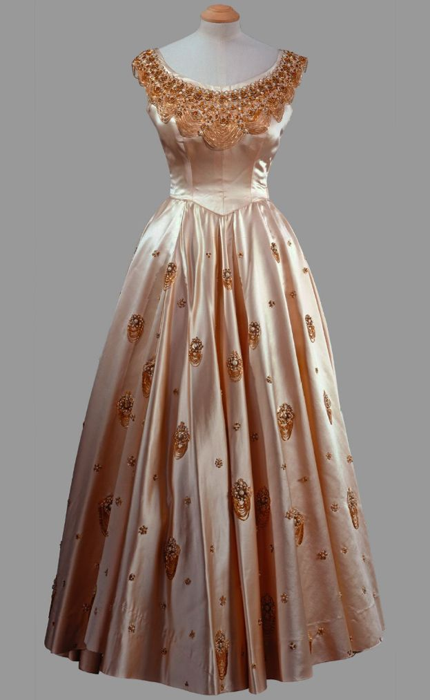 Dress by Norman Hartnell, circa 1956. Cream silk gown with gold looped heavy…