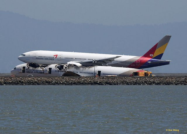 Asiana Airlines flight 214 lands on the runway behind the wreckage of the July 6 flight.