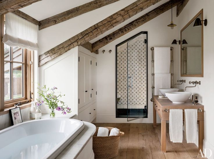 In the master bath of a Martha's Vineyard home designed by architect Mark Hutker and decorator Kathleen Walsh, Lacava basins are paired with Waterworks sink fittings; the shower is lined with Exquisite Surfaces tile.