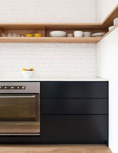 Black cabinetry and unique kitchen storage. Painted brick wall. A la SHED kitchen - desire to inspire
