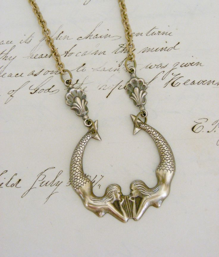 Mermaid Necklace ( Etsy:: http://www.etsy.com/listing/63927217/mermaid-necklace-twin-mermaids-vintage?ref=recently_listed_items# )