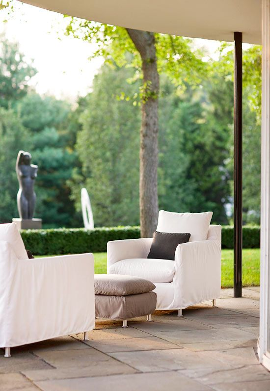 Lee Industries outdoor lounge chairs and an ottoman are slipcovered in Sunbrella fabrics that stand up to wet swimsuits and rainy weather - Traditional Home®