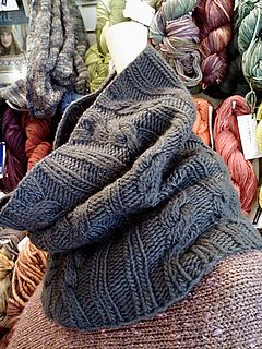 You will need approximately 250 yards of worsted or aran weight yarn. A single-ply yarn or one with some alpaca or silk content will drape best. The cowl is meant to stretch out when blocked.