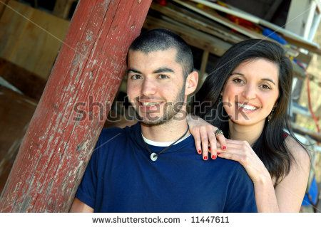 stock photo : Brother and sister pose besides rustic barn post.  Both are smiling.