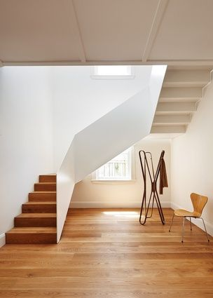 A new white steel stair occupies a void created by the removal of a room on each floor - Manly House by Archer Breakspear