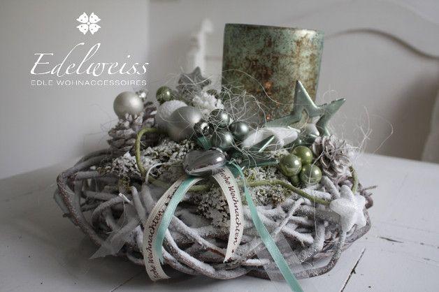 Diese wunderschönes Adventsdeko schmückt ihren Tisch oder ist eine schöne Geschenkidee. Das Gesteck ist aus weisser Weide gefertigt darauf ruhen das große edlen Windlichter in mint/champanger....