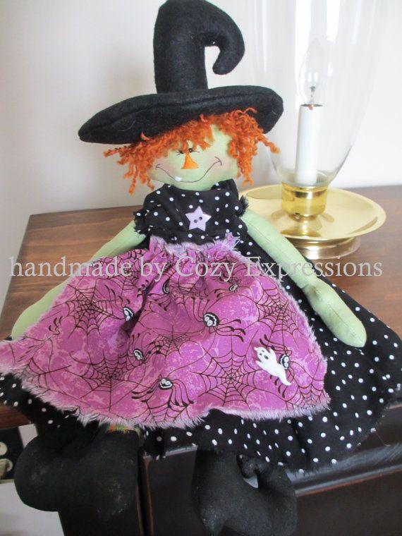 Esta adorable muñeca de la bruja de Halloween es perfecta para tu decoración de Halloween. Ella se ha hecho de día de fiesta algodones de colores.  Su cara, brazos y piernas se hacen de tela verde. Su amplia sonrisa es acentuado por un diente bordado, que se suma a su caprichosa aparición.  Su vestido ha sido creado de la tela impresa punto negro y naranja. Debajo lleva pantalones bombachos de rayas negros y naranja. La blusa del vestido ha sido decorada con un botón naranja. Su plataforma…