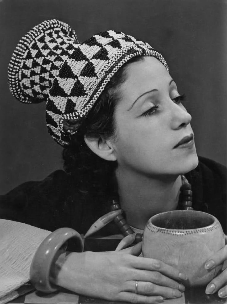 """Madame de St. Exupery, 1937 by Man Ray    Inspired by an exhibition of headdresses from the Belgian Congo at the Galerie Charles Ratton in Paris, Man Ray began photographing women in African hats. In 1937 Harper's Bazaar published four his images from """"La Mode au Congo"""" an in editorial headlined """"The Bushongo of Africa Sends His Hats to Paris."""""""
