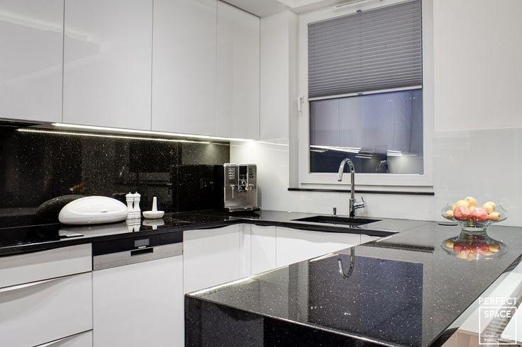 """Aranżacja kuchni w układzie litery """"U"""". Kuchnia w stylu minimalistycznym, gdzie króluje nieśmiertelna biel na frontach szafek kontrastująca z gresową podłogą (Casalgrande Padana) oraz granitowym blatem (Star Galaxy)."""