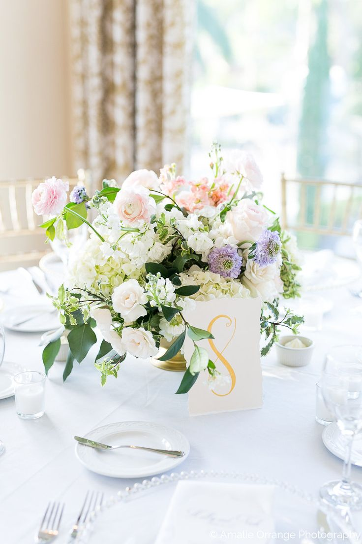 table number calligraphed in gold ink by a lush arrangement of white hydrangea, vendela rose, blushing bride rose, lavender scabiosa, light blue tweedia, peach stock, white stock, variegated pittosporum, dusty miller, english miss spray rose, white ranunculus, pink ranunculus, & greenery in a low gold revere bowl surrounded by votives.
