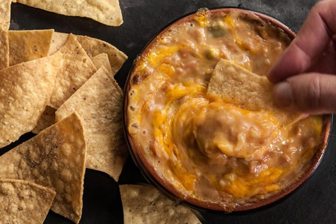 Use crunchy tortillas chips to scoop up this gooey, warm refried bean dip recipe loaded with cheddar cheese and pickled jalapeños.