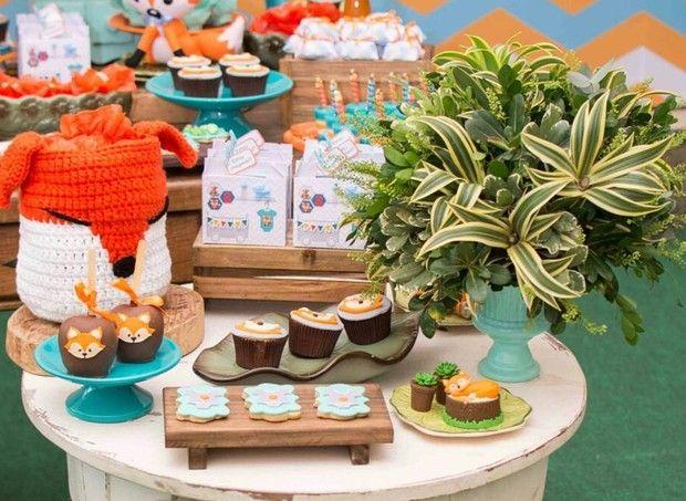 Mesa redonda de madeira rústica com doces no tema da festa e raposa de crochê (Foto: Karina Martini)