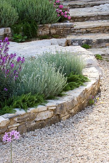Love the low dry stacked wall with gravel for a walkway. - Gardening Design