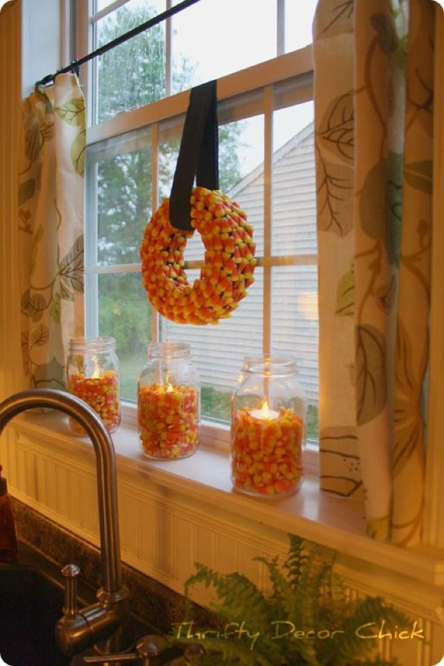 Blogger Sarah of Thrifty Decor Chick created this fall DIY look by adhering candy corn to a styrofoam wreath and filling glass jars with the candies before placing tea light candles inside.