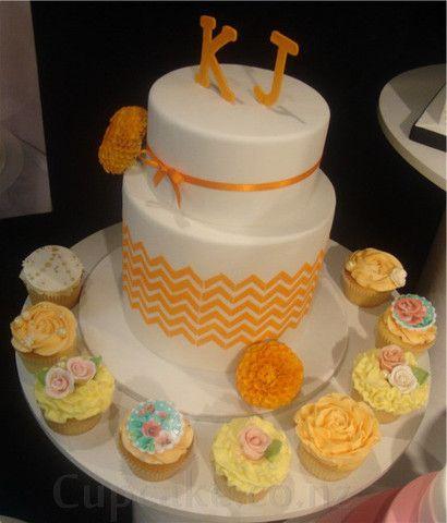 Stunning yellow, orange and white wedding cake with cupcakes