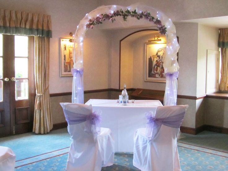 A wedding arch of white voile, ice white lights and a lilac flower garland accentuated the ceremony table for this couple