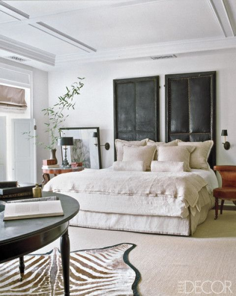 In this master bedroom designed by Darryl Carter antique bordello doors sit behind the bed.