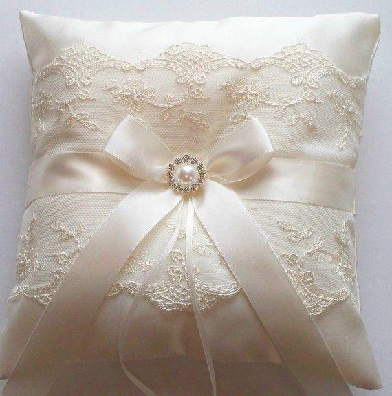 La NICOLE è un cuscino di raso opaco avorio portatore dellanello decorato con doppio pizzo netto avorio capasanta, un fiocco di nastro di raso avorio