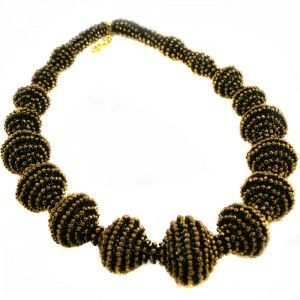 The necklace when straighten looks like hudge snake that has eaten some interesting things and measures 95 cm. Although it is long and looks massive it's very light. It is empty inside and made of glass sead beads.