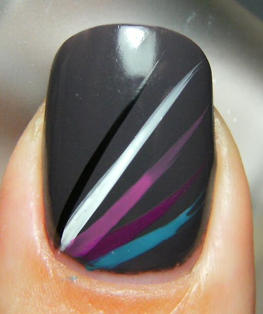 This simple design can be accomplished using a paint brush and acrylic paints. Just lightly flick your brush across your nail at an outward angle. Using acrylics allows you to wash off your mistakes. If you have a steady hand, use nail polish.