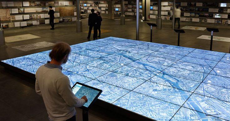 Paris métropole 2020  Touchscreen digital model  Een touchscreen gekoppeld aan een groot scherm (opgebouwd uit meerdere schermen). Om grote hoeveelheden informatie te onsluiten.