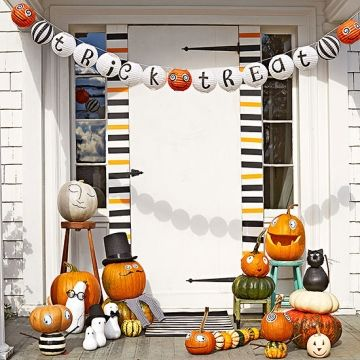 <p>For a festive entrance, cover the door frame with stripes of orange and black masking tape and hang a strand of hand-painted paper lanterns. </p>