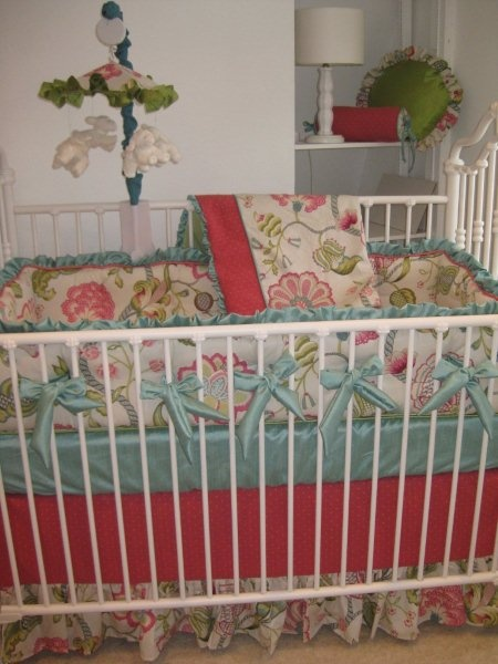 A Musical Mobile And Round Pillows Coordinate With The Aqua Melon Fl Crib Bedding