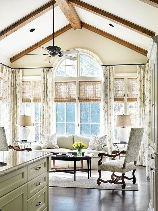 A sitting room just off the kitchen is outfitted in the same creams and taupes, tying the two rooms together. Light-color fabrics are balanced by dark wood furniture and a ceiling with wood beams.