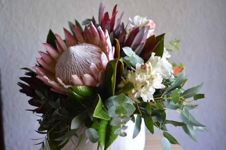 A beautiful mix of king protea, roses, leucadendron, tuberose, chrysanthemum, repen protea in a marbled pot view 1