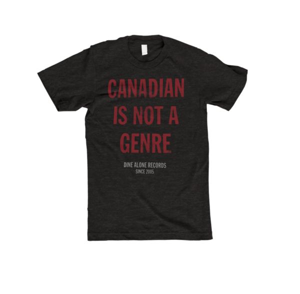 Canadian T-Shirt (Charcoal) This super soft, charcoal black triblend t-shirt features the saying Canadian Is Not A Genre on the front in a burgundy print.