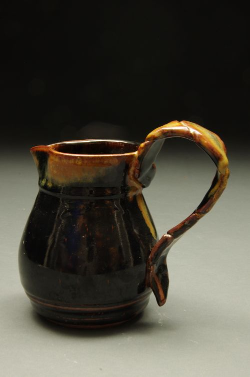 Lovely jug with a delicate looking handle. Handle was folded over itself before being attached to give a unique look. Red stoneware reduction fired to Cone 10 Available for purchase