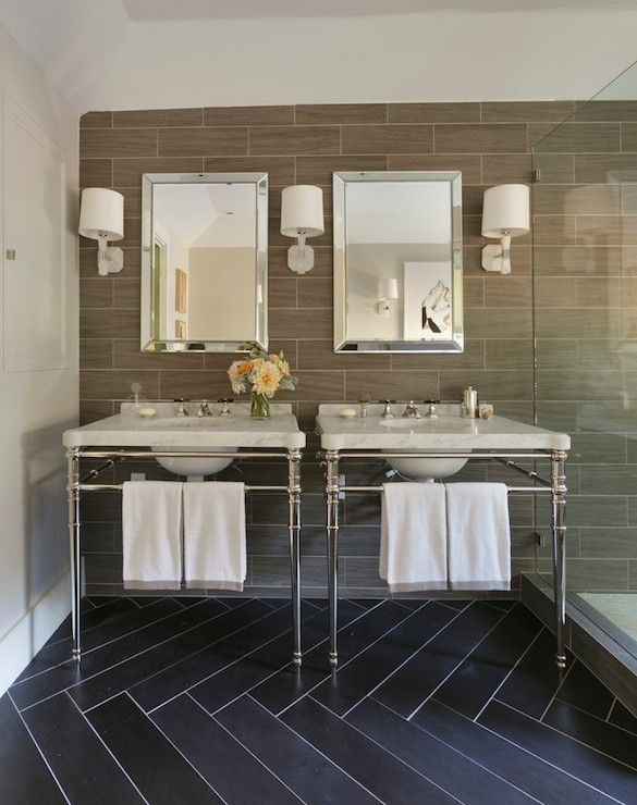 """""""Chrome his and her washstand with ivory marble countertops below beveled vanity mirrors flanked by marble wall sconces with drum shades. The bathroom features a black herringbone tiled floor accented with white grout alongside a ceiling height backsplash wall tiled in a gray wood grain tile backsplash by Crossville which flows seamlessly into the glass framed shower to the right of the washstand sinks."""""""