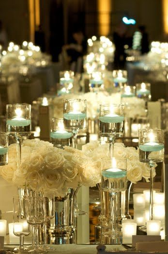 All white flowers are brightened up with glowing pale blue floating candles in tall vases! Simple but gorgeous!