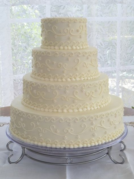 This cake is iced smooth with buttercream. Scrolls and edible pearls accent the cake to replicate a wedding dress design.