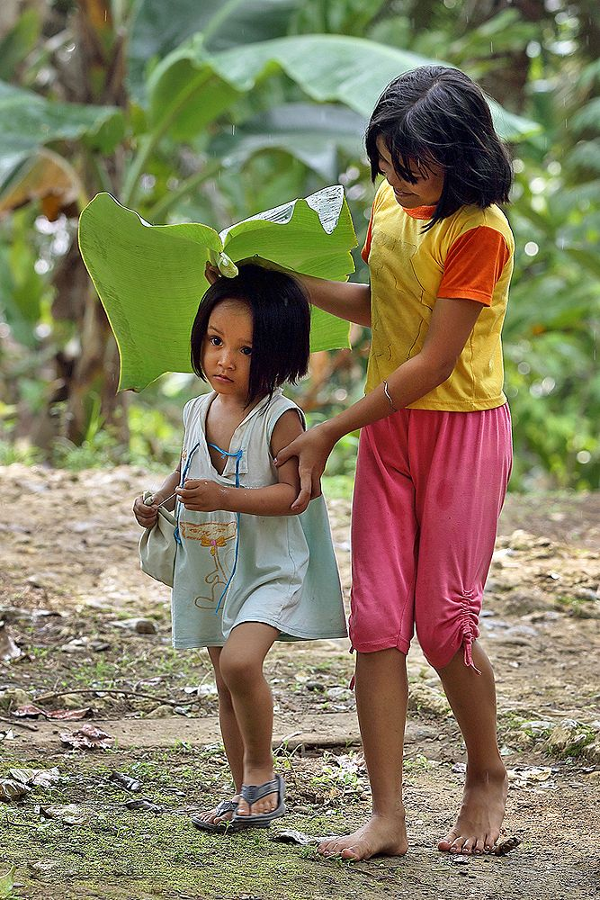 Nias Umbrella; a girl is covering her younger sister with a banana-leaf. North Nias Regency, Nias Island, Indonesia. Photo by Bjorn Svensson. www.northniastourism.com