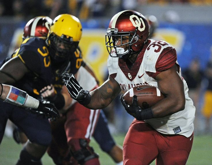 Oklahoma's Samaje Perine (32) reaches to stiff-arm a West Virginia defender during the fourth quarter of an NCAA college football game in Morgantown, W.Va., Saturday, Sept. 20, 2014. (AP Photo/Tyler Evert)