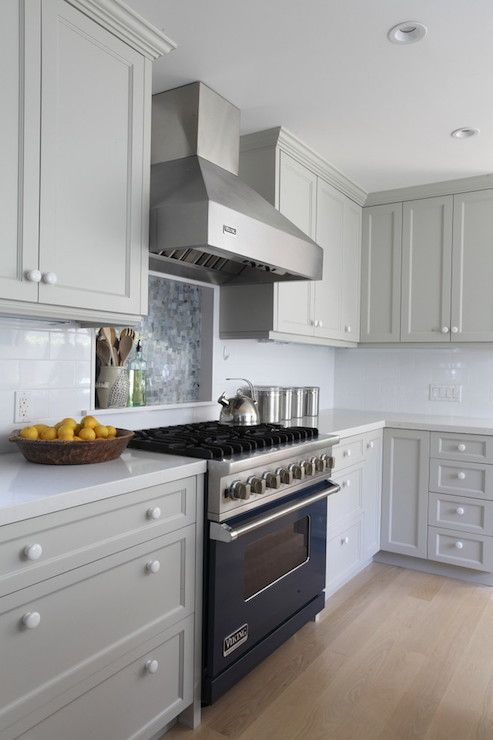 Ben Moore Brushed Aluminum gray cabinet #paint, light gray counters, blue range, cooktop wall niche w/blue tile