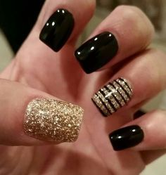 black and gold manicure with a gold nails and a striped accent one