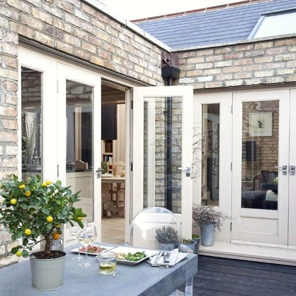 french doors. ghost chairs on the patio. weathered brick.