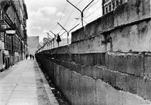 De berlijnse muur van dik beton en een omheining van prikkeldraad.
