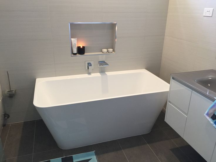 This full bathroom renovation transformed the room into a modern masterpiece. Great interior design with all the latest bathroom products from Highgrove Bathrooms. Freestanding bath with waterfall spout and shower niche.