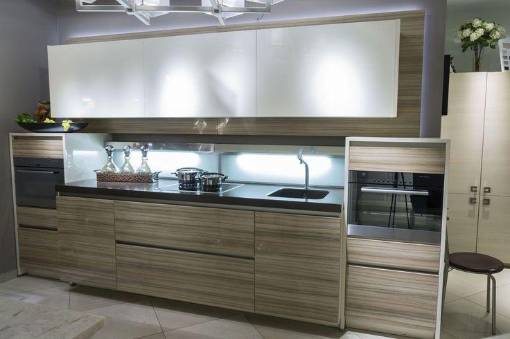 Кухня Bauformat линейной конфигурации с глянцевыми фасадами COCO-BOLO на нижнем ряду шкафов. Недорогие фасады COCO-BOLO прекрасно смотрятся за счет расцветки, имитирующей текстуру экзотической древесины. Верхний ряд шкафов с фасадами молочно-белого цвета сочетаются с основным колоритом кухни #bauformat