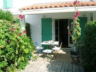 A French cottage terrace, with hollyhocks lining the green shutters.