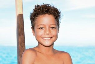 Young boy for family photography in Fiji at Cloud 9 with turquoise blue water sea in the background. By Anais Photographer in Fiji.