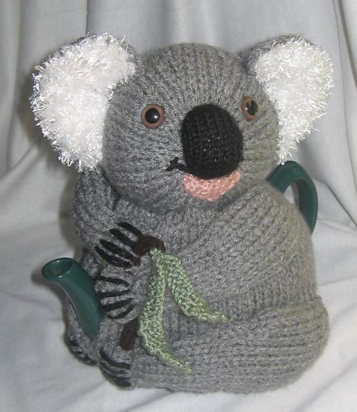 """I made this one twice in different poses – I designed him so that he could be made to sit in a variety of ways to look like a real koala. (I really dislike that """"cruciform koala"""" look!) He's very cute and would make a great gift!He takes about 135 gms of your choice of DK/8 ply yarn (used double), plus 10 gms of something fluffy/furry for the ears. You also need a small mount of black, green, brown and pink.This pattern makes a tea cosy to fit a teapot approx 15 cms high and 46 cm around…"""