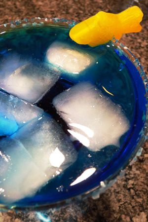 Shark Infested Water Ingredients: 2 parts margarita mix. 2 parts tequila. 1 part blue curacao. 1 part triple sec. Salt. Blue sugar. Gummy fish or gummy sharks. Directions: Garnish a margarita glass with salt, blue sugar, and a gummy fish. Fill the glass with ice. Mix the remaining ingredients in a cocktail shaker or pitcher and pour into the glass.