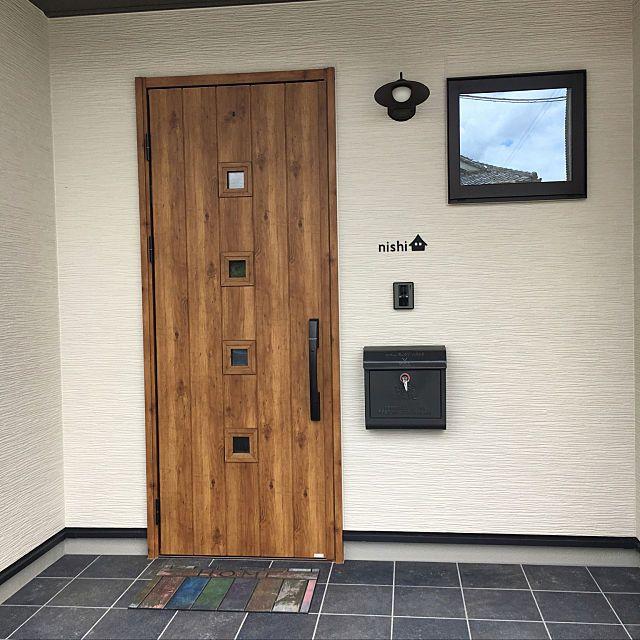 シルバーの金属感がある壁面と 濃いブラウンカラーの玄関ドア 窓
