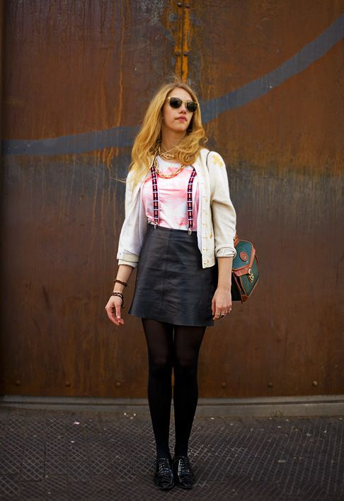 Very cool leather skirt with suspenders, a white cardigan, green purse, black tights and black Oxford shoes.
