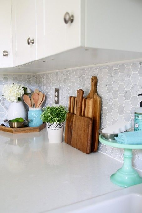 Kitchen accessories, cutting boards, Carra marble backsplash. Beautiful white IKEA SEKTION GRIMSLOV kitchen with aqua and green accents, a gorgeous marble hexagon backsplash, and quartz countertops. | JustAGirlAndHerBlog.com Splashback